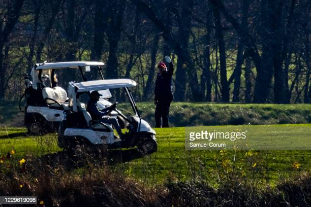 President Donald Trump waves as he plays golf at his club, Trump National Golf Club, on November 14, 2020 in Sterling, Virginia. The President is...