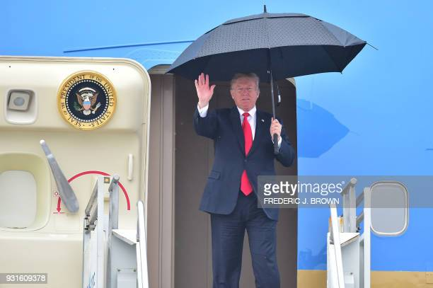 US President Donald Trump waves as he shelters from the rain under an umbrella as he disembarks from Airforce One in Los Angeles California on March...