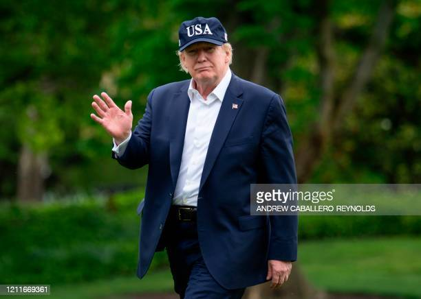 US President Donald Trump waves as he walks from Marine One to the White House on May 3 2020 in WashingtonDC after returning from Camp David Donald...