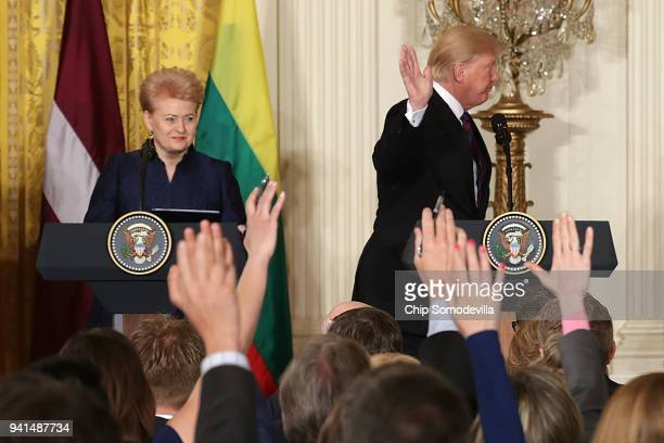 President Donald Trump waves as he walks off stage following a news conference with Lithuanian President Dalia Grybauskaite , Estonian President...