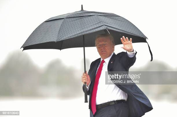 US President Donald Trump waves as shelters from the rain under an umbrella as he arrives in Los Angeles California on March 13 2018