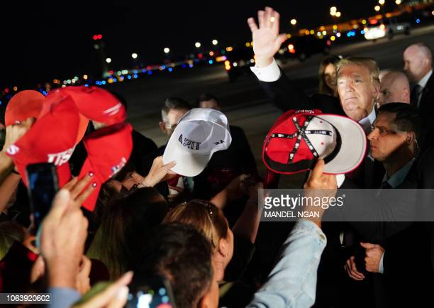 US President Donald Trump waves as signs autographs upon arrival at Palm Beach International Airport in West Palm Beach Florida on November 20 2018...