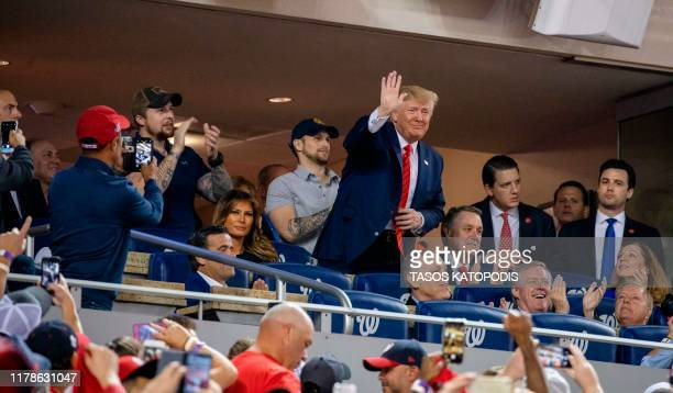 US President Donald Trump waves as US First Lady Melania Trump looks on as they watch Game 5 of the World Series between the Washington Nationals and...
