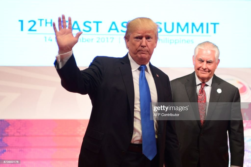 US President Donald Trump (L) waves as US Secretary of State Rex Tillerson looks on after attending the 31st Association of Southeast Asian Nations (ASEAN) Summit in Manila on November 14, 2017. The US president is in the Philippines with leaders of 18 other nations for two days of summits, the final leg of a headline-grabbing Asian tour dominated by the North Korean nuclear crisis. /