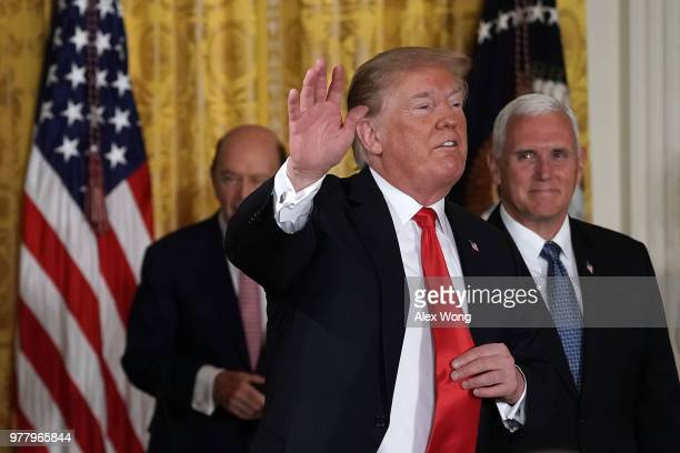 S President Donald Trump waves as Vice President Mike Pence and Secretary of Commerce Wilbur Ross look on during a meeting of the National Space...