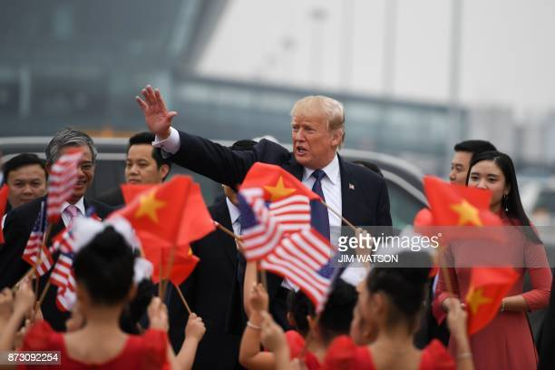 US President Donald Trump waves as young girls wave US and Vietnamese national flags before boarding Air Force One to depart to the Philippines at...