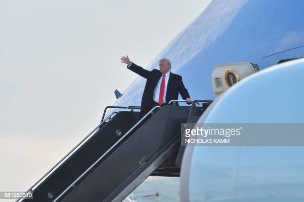 US President Donald Trump waves from Air Force One as he departs St Louis Lambert International Airport in St Louis Missouri November 29 2017 / AFP...