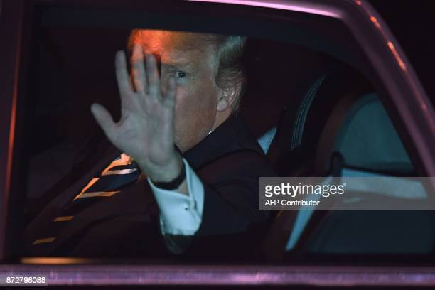 US President Donald Trump waves from the presidential limo nicknamed The Beast following his arrival at Hanoi's Noi Bai airport on November 11 2017...
