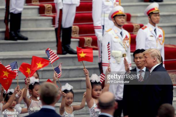 President Donald Trump waves hands to Vietnamese children during a welcome ceremony at the Presidential Palace in Hanoi on November 12, 2017. Trump...
