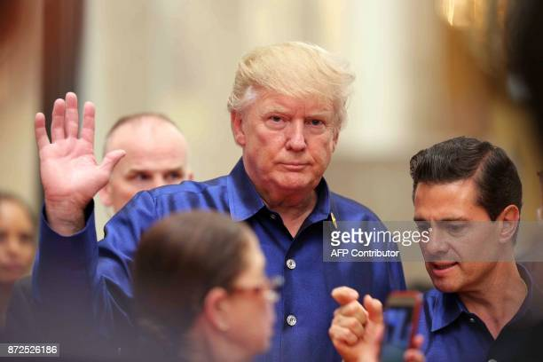 US President Donald Trump waves next to Mexico's President Enrique Pena Nieto ahead of the AsiaPacific Economic Cooperation Summit leaders gala...