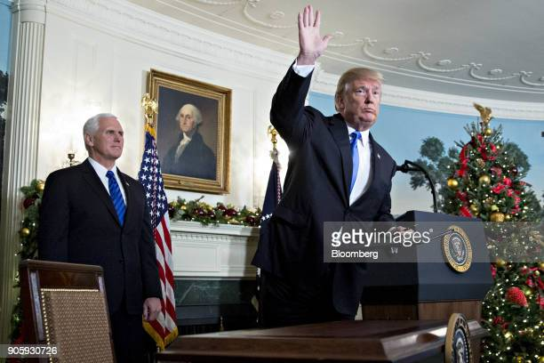 S President Donald Trump waves next to US Vice President Mike Pence left after making a statement on Jerusalem in the Diplomatic Room of the White...