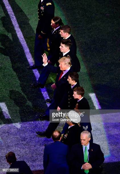 S President Donald Trump waves to fans as he walks on the field prior to the CFP National Championship presented by ATT between the Georgia Bulldogs...