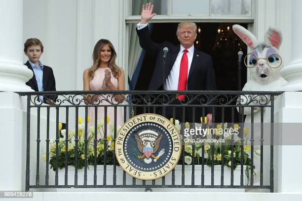 S President Donald Trump waves to guests after delivering remarks from the Truman Balcony with first lady Melania Trump and their son Barron Trump...