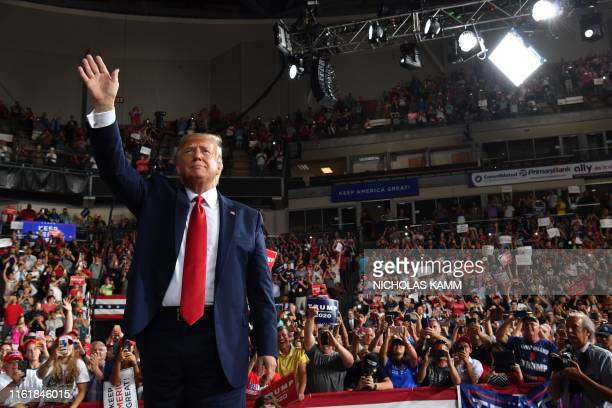 US President Donald Trump waves to his supporters after a Keep America Great campaign rally at the SNHU Arena in Manchester New Hampshire on August...
