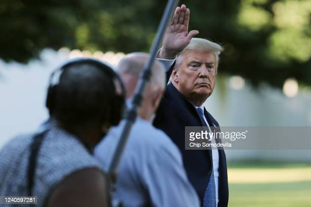 S President Donald Trump waves to journalists as he returns to the White House after posing for photographs in front of St John's Episcopal Church...
