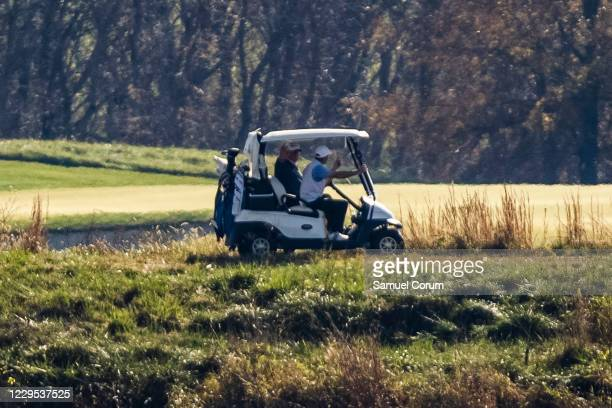 President Donald Trump waves to media across the Potomac River as he plays a round of golf at his private club, Trump National Golf Club, on November...