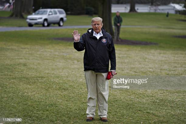 US President Donald Trump waves to members of the media while waiting for US First Lady Melania Trump and son Barron Trump not pictured on the South...