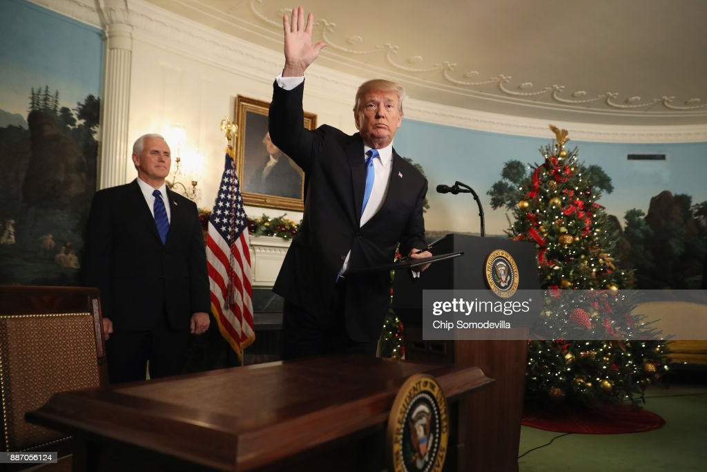 US President Donald Trump waves to reporters, as Vice President Mike Pence (L) looks on, after announcing that the U.S. government will formally recognize Jerusalem as the capital of Israel in the Diplomatic Reception Room at the White House December 6, 2017 in Washington, DC. In keeping with a campaign promise, Trump said the United States will move its embassy from Tel Aviv to Jerusalem sometime in the next few years. No other country has its embassy in Jerusalem.