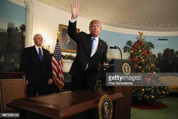 President Donald Trump waves to reporters as Vice President Mike Pence looks on after announcing that the US government will formally recognize...