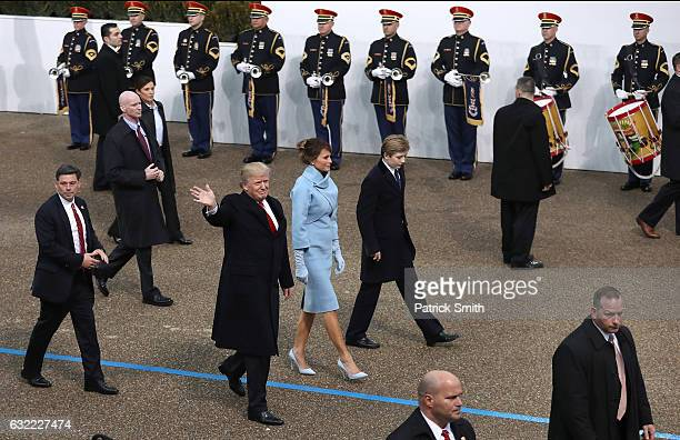 US President Donald Trump waves to supporters as he walks the parade route with first lady Melania Trump and son Barron Trump past the main reviewing...