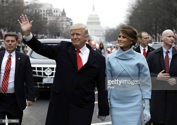 S President Donald Trump waves to supporters as he walks the parade route with first lady Melania Trump after being sworn in at the 58th Presidential...