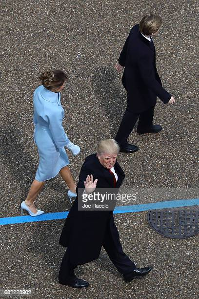 S President Donald Trump waves to supporters as he walks the parade route with first lady Melania Trump and son Barron Trump during the Inaugural...