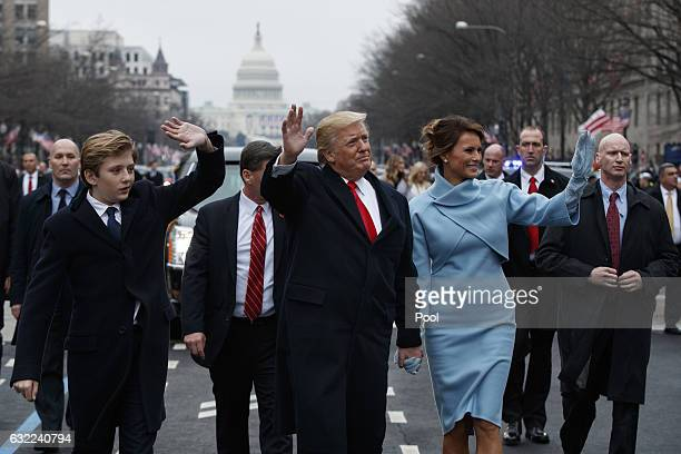 S President Donald Trump waves to supporters as he walks the parade route with first lady Melania Trump and son Barron Trump after being sworn in at...