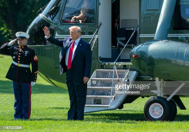 President Donald Trump waves to supporters before departing from the White House on the south lawn before he boards Marine One on August 09 2019 in...