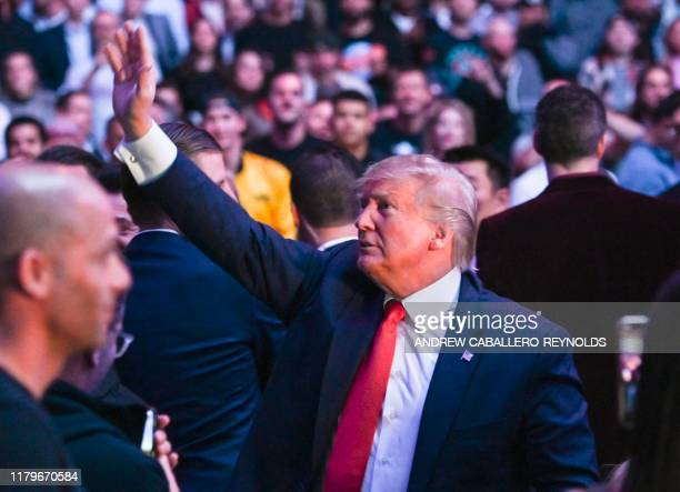 US President Donald Trump waves to the crowd as he attends the Ultimate Fighting Championship at Madison Square Garden in New York City New York on...