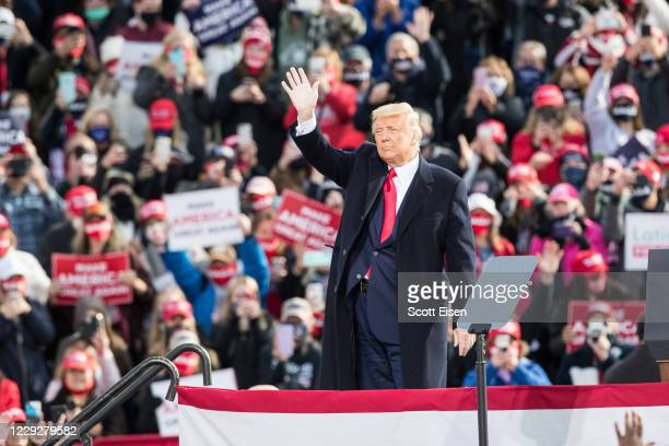 President Donald Trump waves to the crowd at the end of a campaign rally on October 25, 2020 in Londonderry, New Hampshire. President Trump continues...