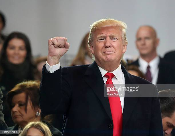 S President Donald Trump waves to the crowd from the inaugural parade revieing stand in front of the White House on January 20 2017 in Washington DC...