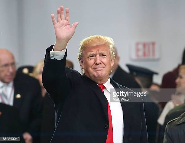 S President Donald Trump waves to the crowd from the inaugural parade reviewing stand in front of the White House on January 20 2017 in Washington DC...