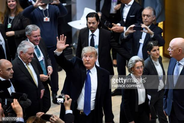 President Donald Trump waves upon his arrival with Secretary of State Rex Tillerson for the World Economic Forum annual meeting in Davos eastern...
