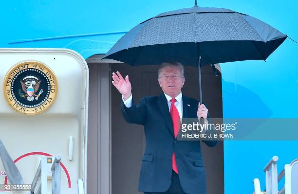 US President Donald Trump waves while holding an umbrella disembarking from Airforce One on arrival in Los Angeles California on March 13 2018