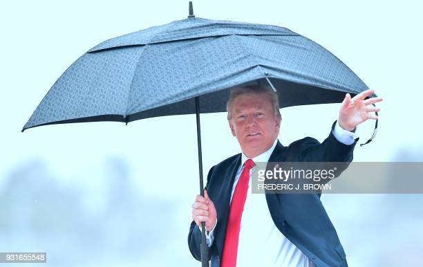 US President Donald Trump waves while holding his umbrella walking under the rain on arrival in Los Angeles California on March 13 2018