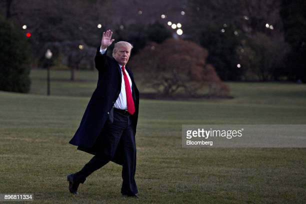 US President Donald Trump waves while walking on the South Lawn of the White House after landing in Washington DC US on Thursday Dec 21 2017 Trump...
