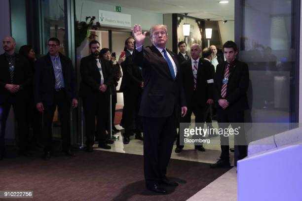US President Donald Trump waves while walking through the Congress Center on day three of the World Economic Forum in Davos Switzerland on Thursday...