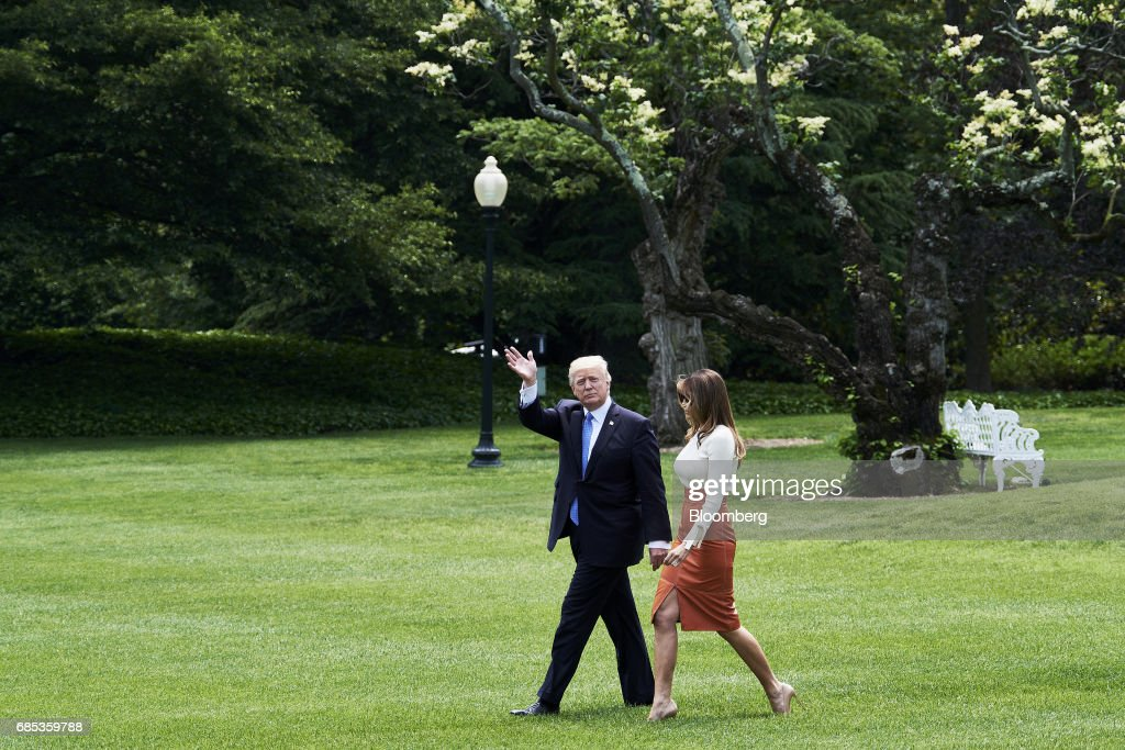 U.S. President Donald Trump waves while walking towards Marine One with First Lady Melania Trump on the South Lawn of the White House in Washington, D.C., U.S., on Friday, May 19, 2017. Trumpdeparted Friday for his first foreign trip as president with his White House engulfed in crisis and little prospect for a break from the drama disrupting his agenda. Photographer: T.J. Kirkpatrick/Bloomberg via Getty Images