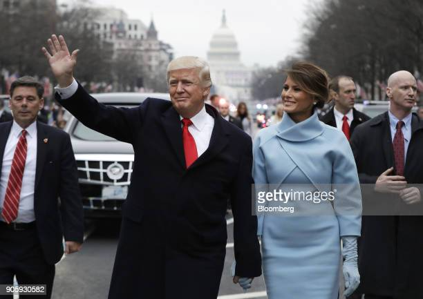 S President Donald Trump waves while walking with US First Lady Melania Trump during a parade following the 58th presidential inauguration in...
