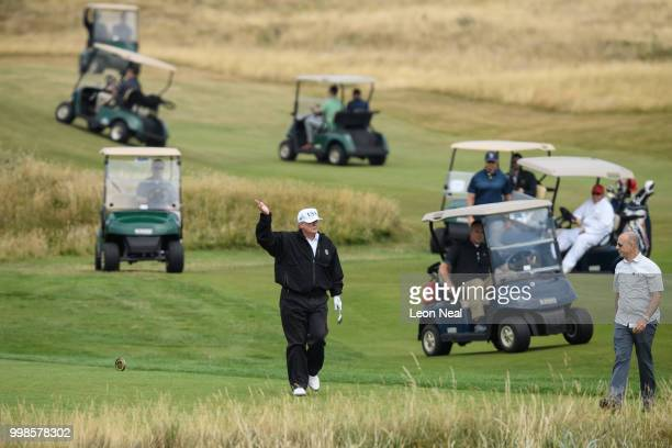 S President Donald Trump wearing a hat with Trump and USA displayed on it plays golf at Trump Turnberry Luxury Collection Resort during the...