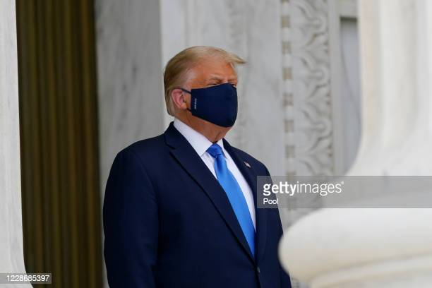 President Donald Trump wears a face mask while he pays his respects as Justice Ruth Bader Ginsburg lies in repose under the Portico at the top of the...