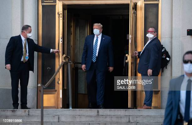 President Donald Trump wears a facemask as he walks out of Walter Reed Medical Center in Bethesda, Maryland before heading to Marine One on October 5...