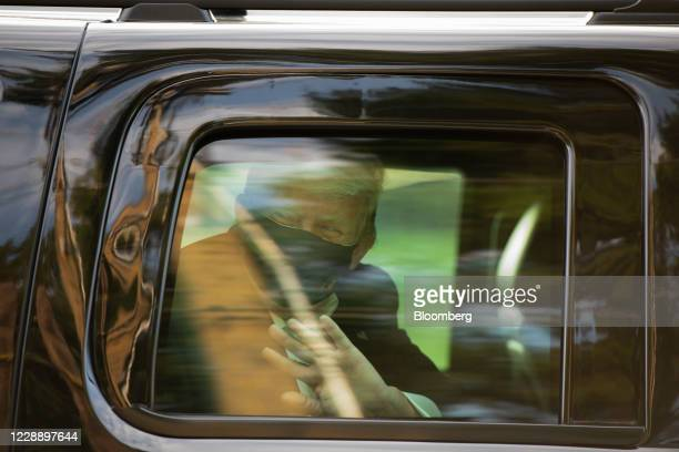 President Donald Trump wears a protective mask while waving as he is driven in a motorcade past supporters outside of Walter Reed National Military...