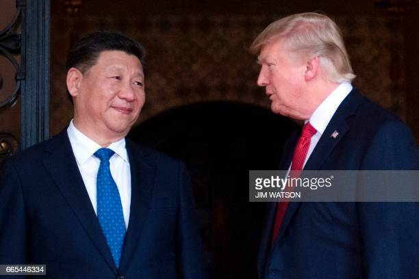 US President Donald Trump welcomes Chinese President Xi Jinping to the MaraLago estate in West Palm Beach Florida on April 6 2017 / AFP PHOTO / JIM...