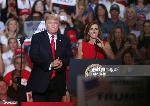 President Donald Trump welcomes Rep Martha McSally RAriz to the stage during a rally at the International Air Response facility on October 19 2018 in...