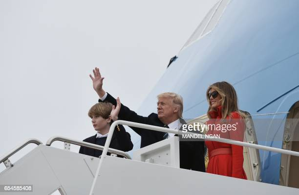 US President Donald Trump wife Melania and son Barron wave while boarding Air Force One before departing from Andrews Air Force Base in Maryland on...