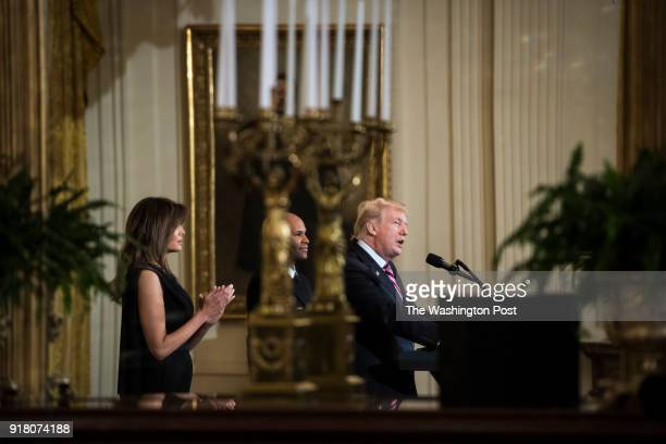 President Donald Trump with first lady Melania Trump and Surgeon General Jerome Adams center seen reflected in a mirror speaks during a National...