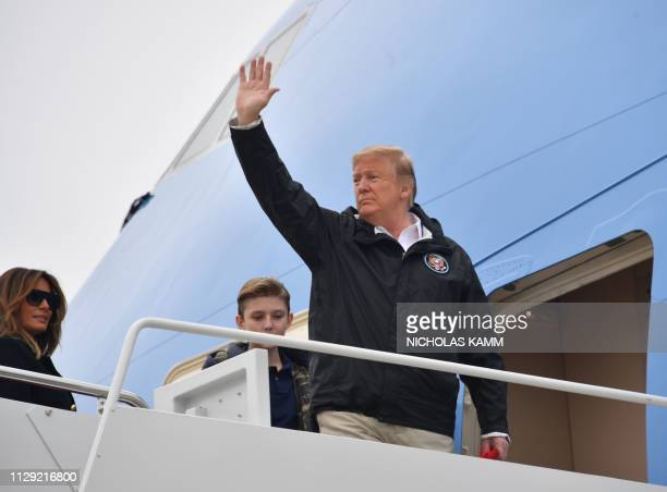 US President Donald Trump with First Lady Melania Trump and their son Barron waves as he boards Air Force One at Joint Base Andrews in Maryland on...