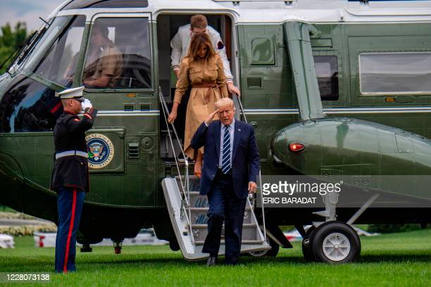US President Donald Trump with First Lady Melania Trump and their son Barron return to the White House after a weekend in Bedminster on August 16...