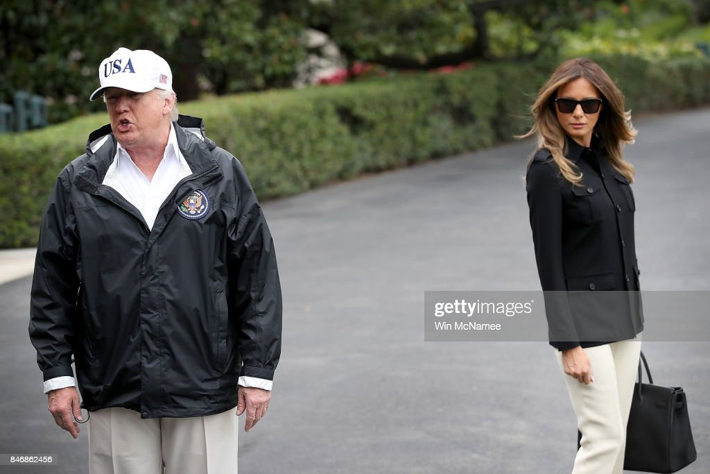 U.S. President Donald Trump, with first lady Melania Trump, answers questions while departing the White House September 14, 2017 in Washington, DC. Trump spoke on reports from a meeting with Democratic leaders last night about a proposed deal on DACA and potentially delaying negotiations on his efforts to build a wall on the U.S. border with Mexico. Trump is scheduled to visit Florida today to view relief efforts in the wake of Hurricane Irma.